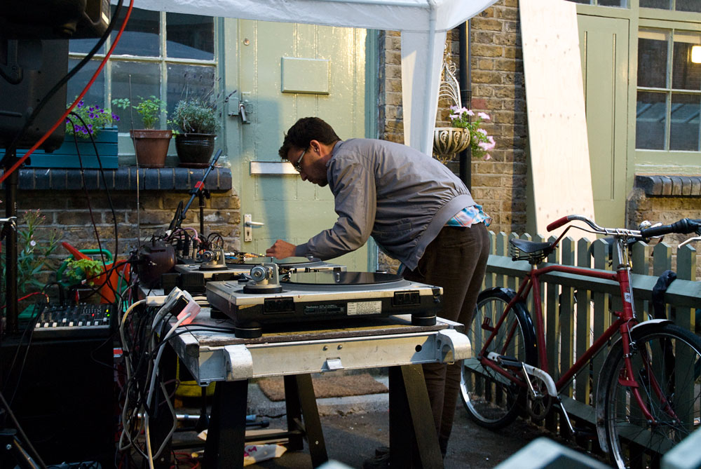 musician performing on turntables outdoors under a tent