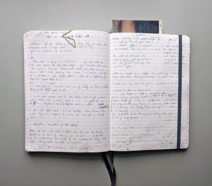 double spread of a notebook showing handwriting and bookmark