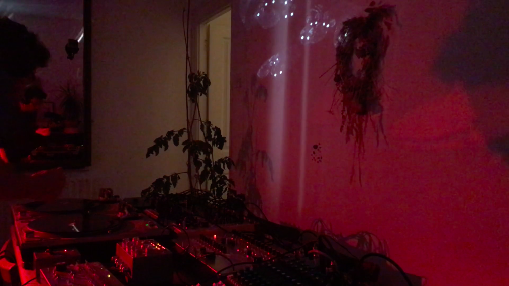 room lit with low pink light showing musician in front of synthesisers and turntables
