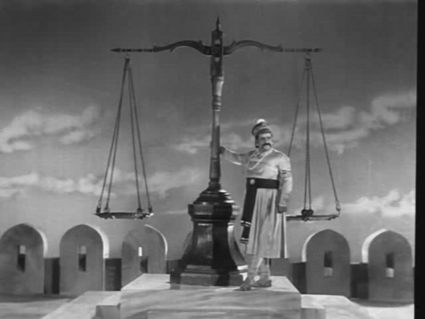 black and white film still showing a tall man in traditional south asian dress resting against a human sized set of weighing scales