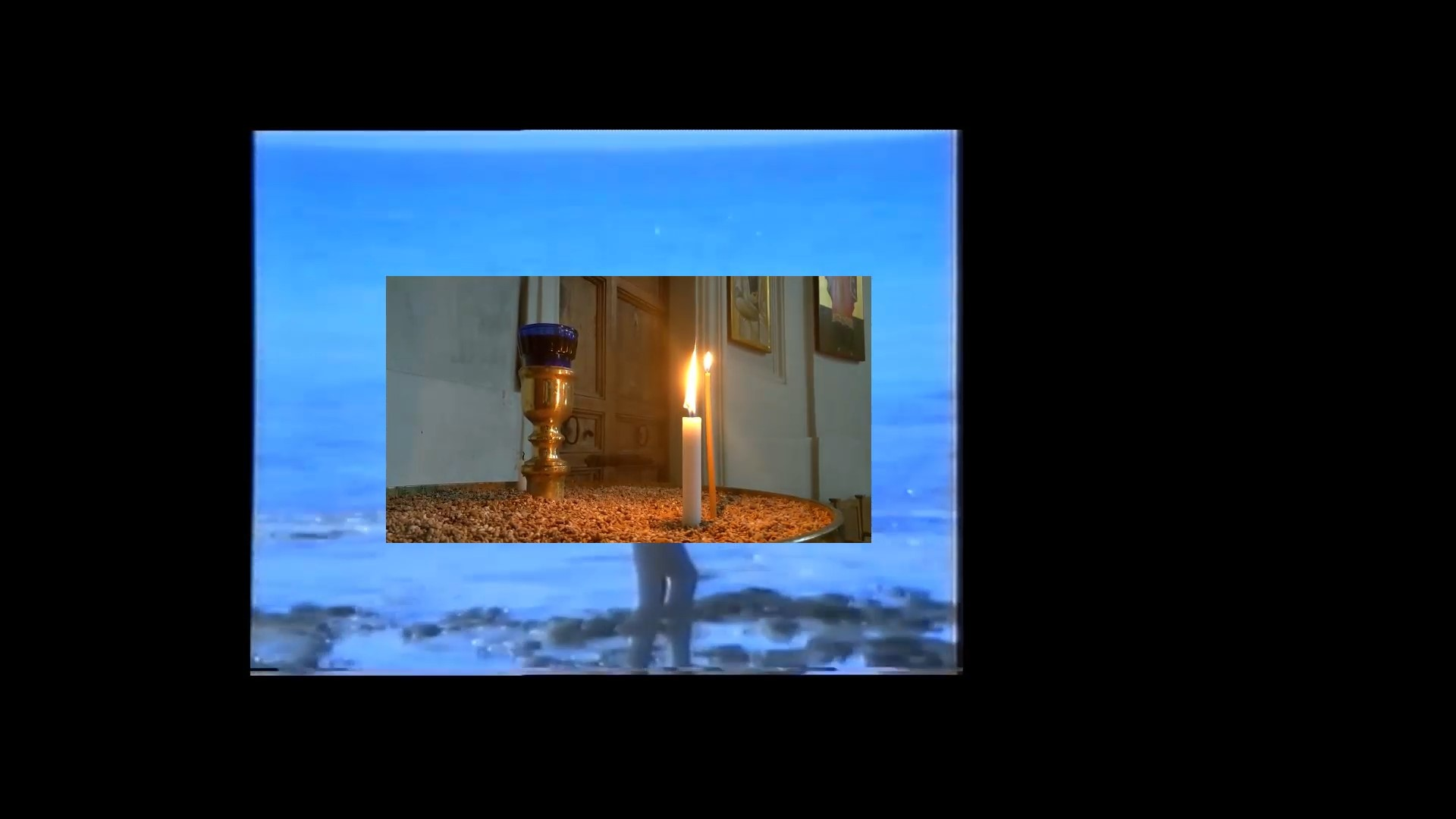 lit candles in a shrine superimposed on an image of a figure walking along a darkened shoreline