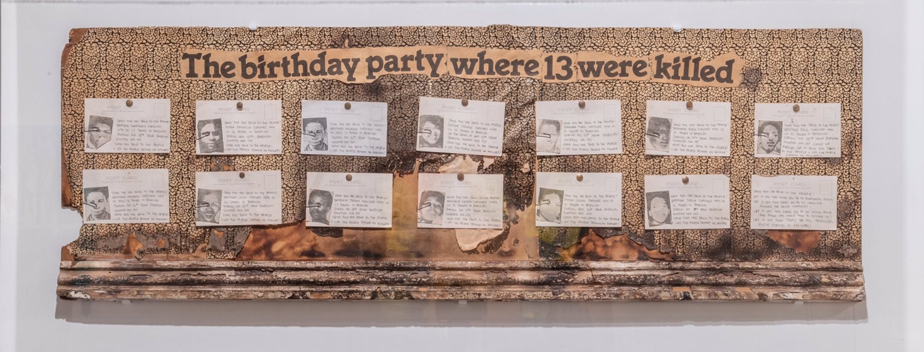 documentation showing photos of 13 young people under the heading 'the birthday party where 13 were killed' against a smoke damaged replica wall and skirting board